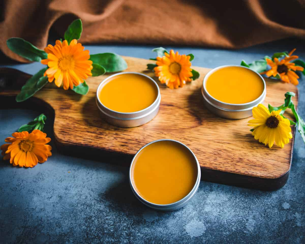 tins of calendula infused oil on a wooden cutting board