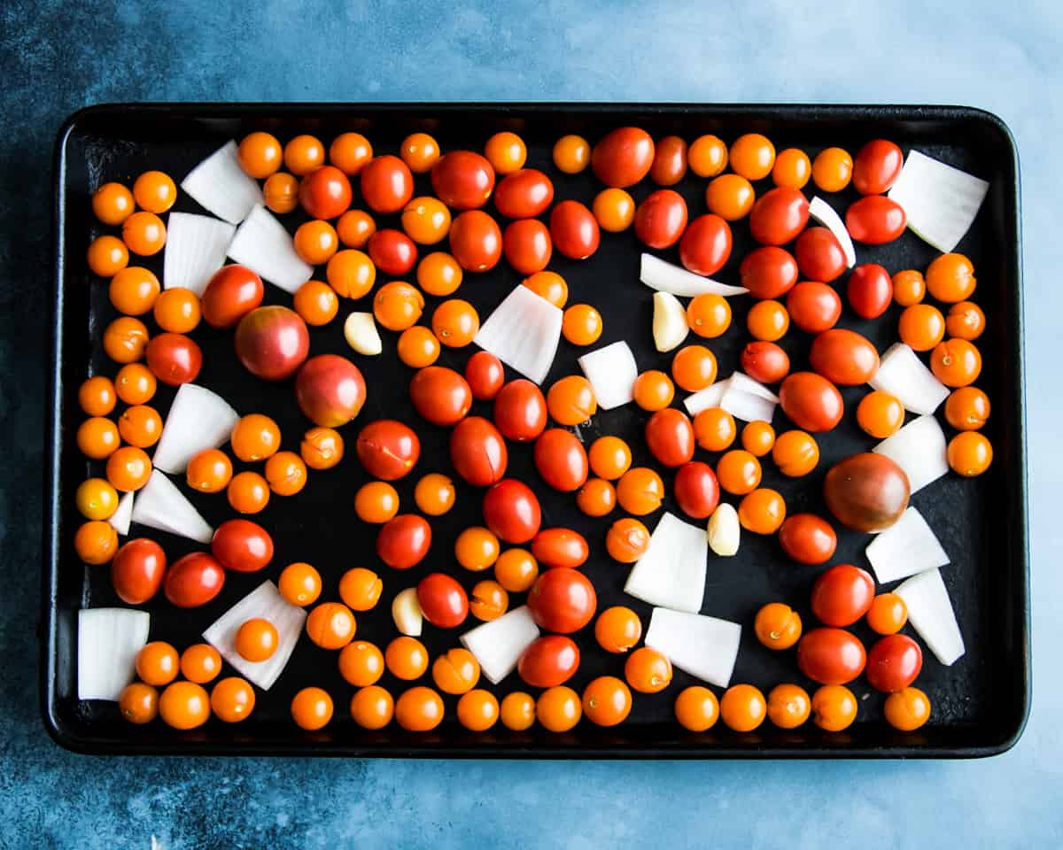 a sheet pan with cherry tomatoes, onions and garlic