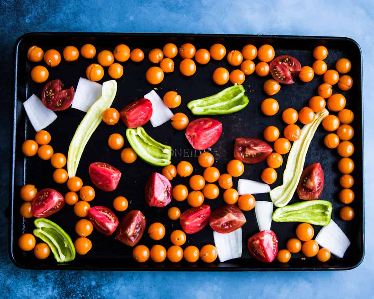 a sheet pan with tomatoes and peppers