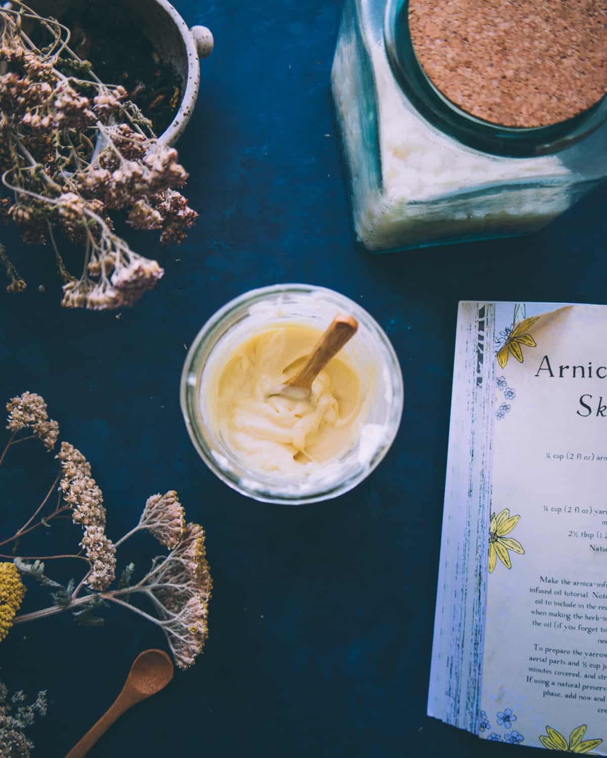 Top view of jar filled with arnica and yarrow cream, with a wooden spoon standing up in it as if it had just been stirred. On a navy blue countertop surrounded by the recipe book and dried yarrow flowers.