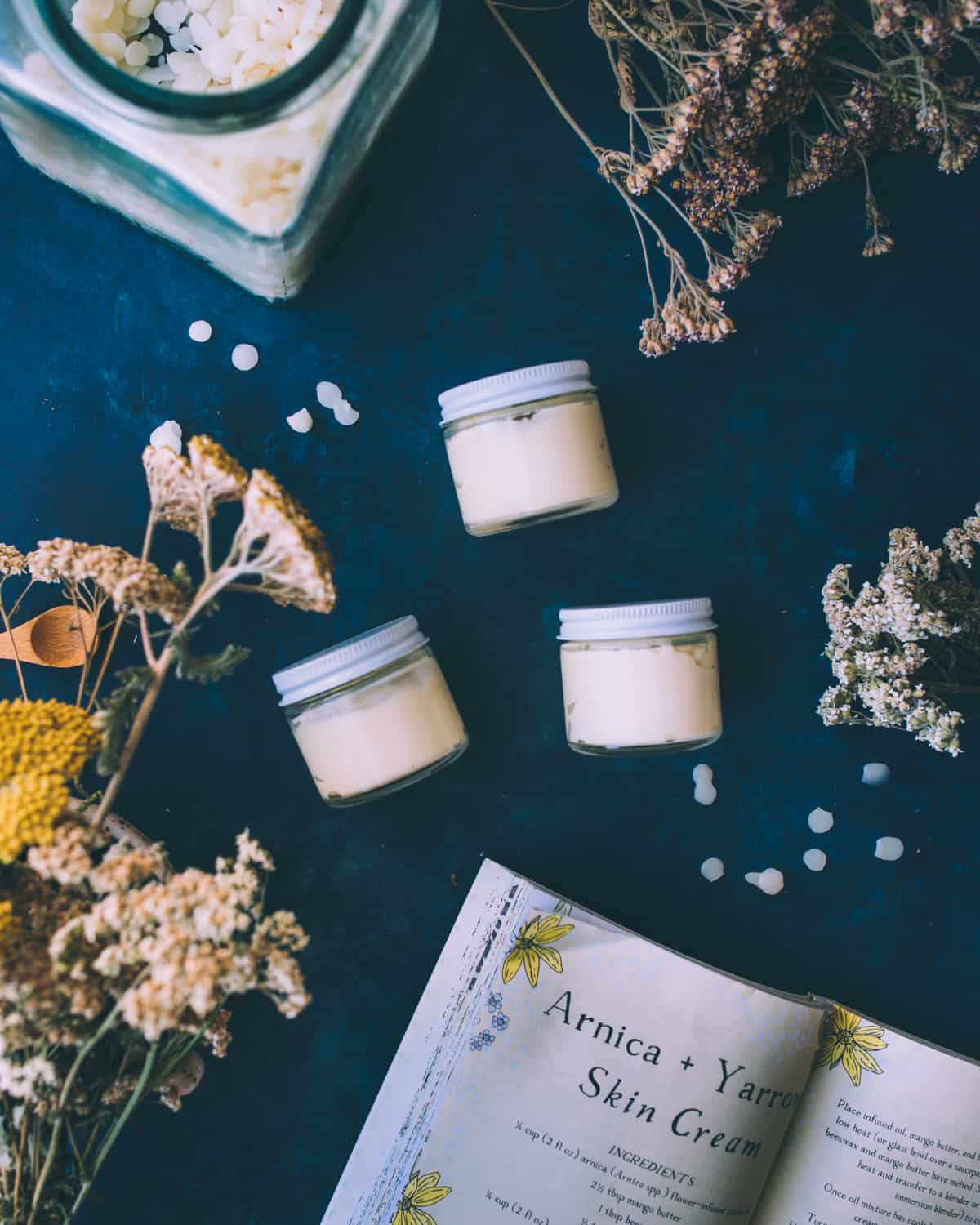 3 small jars with lids on, resting on their sides and filled with arnica and yarrow cream. On a navy blue countertop surrounded by the recipe book open to the page showing arnica and yarrow skin cream recipe, and dried yarrow flowers.