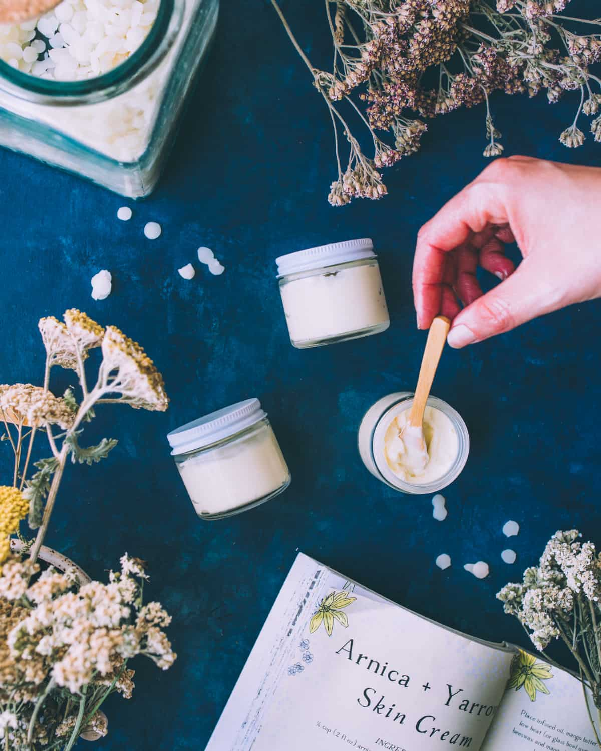 2 jars resting on their sides filled with the cream, and one open top view with a hand stirring the arnica and yarrow cream with a tiny wooden spoon. On a navy blue countertop surrounded by the recipe book and dried yarrow flowers.