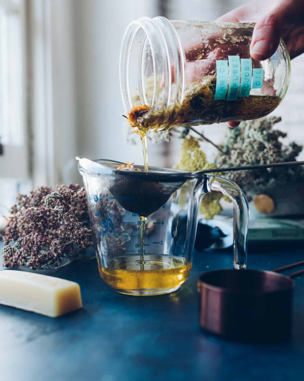 A labeled jar of infused arnica flower oil pouring into a strainer resting in a clear dish, straining the arnica flowers from the oil. On a dark counter, with dried yarrow and a stick of beeswax in the background.