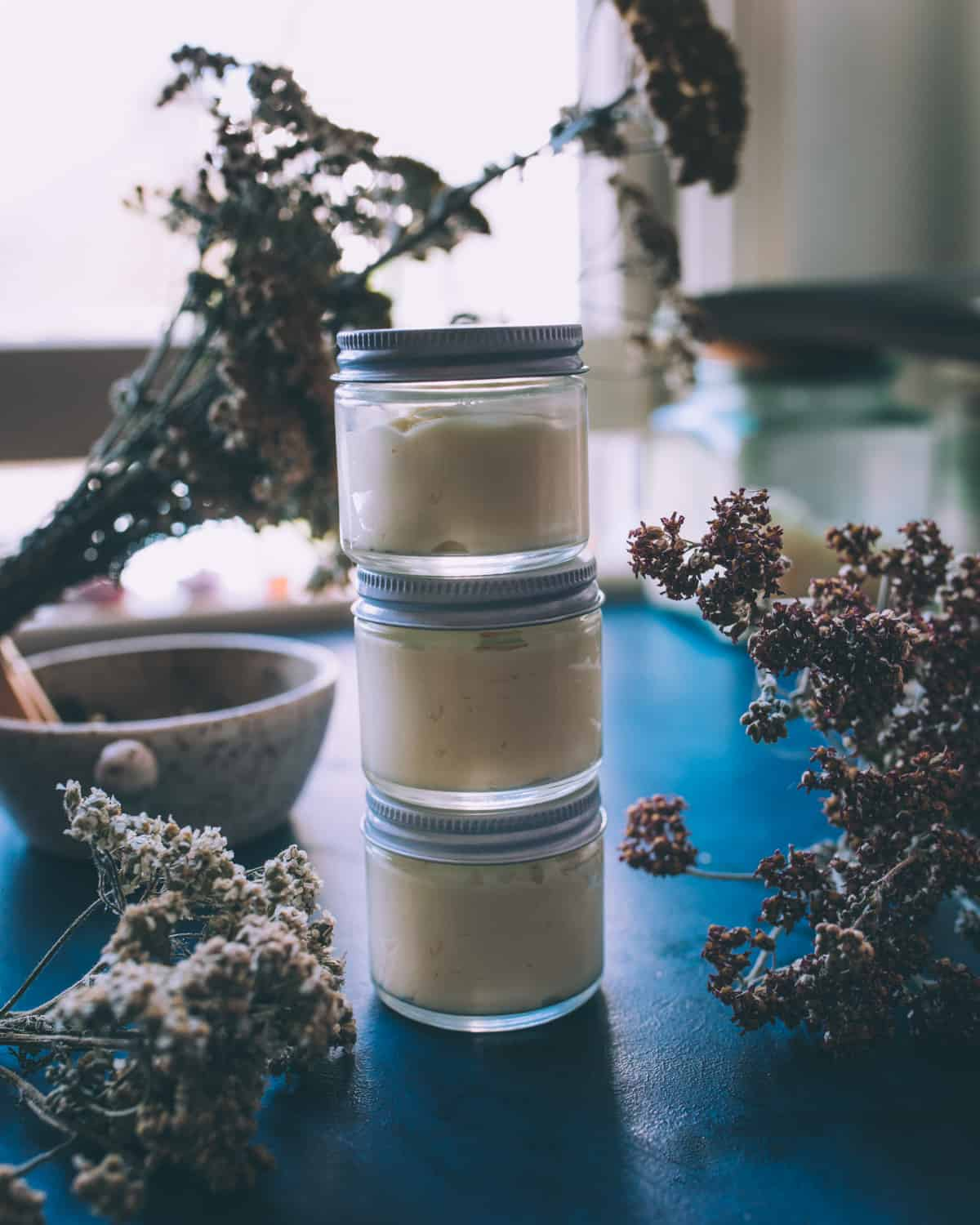 A stack of 3 small jars with lids on, filled with finished arnica and yarrow cream. Sitting on a dark blue counter top with dried yarrow flowers and a mortar and pestle in the background.
