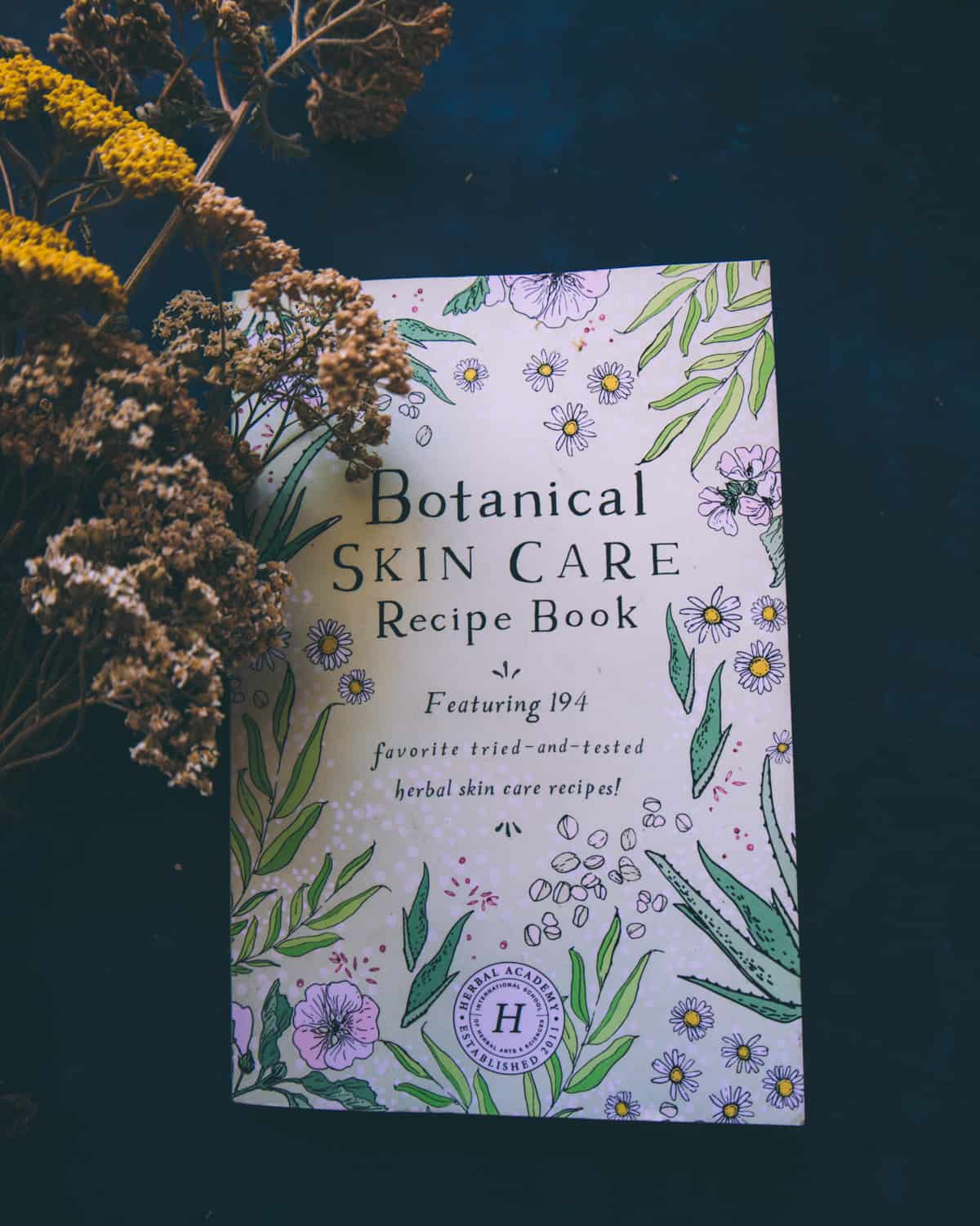 """Dark background featuring a light purple book cover with darker purple flowers and their green leaves surrounding the book title that reads """"Botanical Skin Care Recipe Book featuring 194 favorite tried-and-tested herbal skincare recipes"""""""