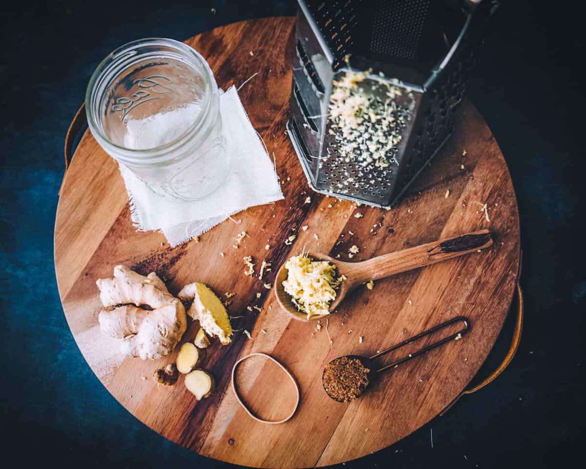 fresh ginger, a jar, a cheese grater, and spoons of ginger and sugar on a round wooden board