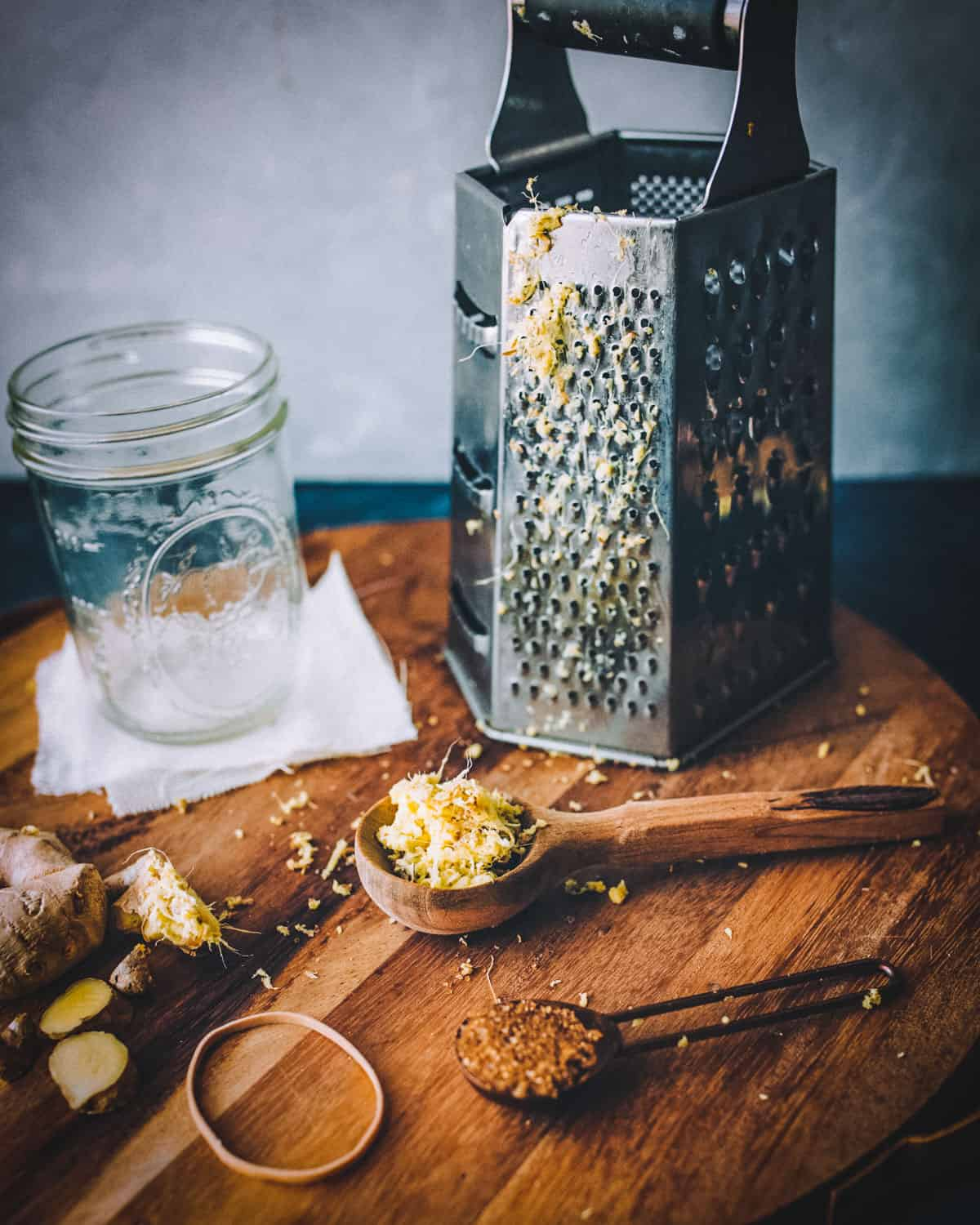 a cheese grater and a wooden spoon of grated ginger
