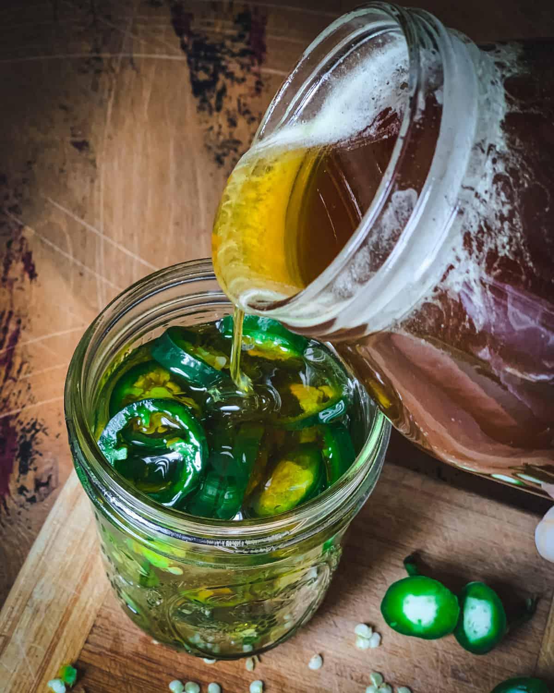 Big jar of honey pouring into smaller jar of sliced jalapeños.