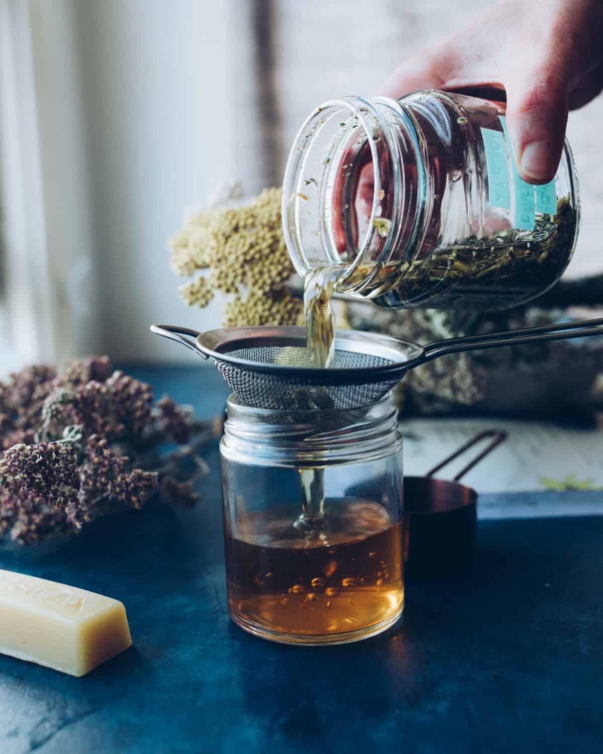 Jar of yarrow flower infused tea water, pouring into a strainer held by a clear jar. The jar is half full of strained yarrow water. On a dark blue counter top, with dried yarrow flowers and a stick of beeswax in the background.