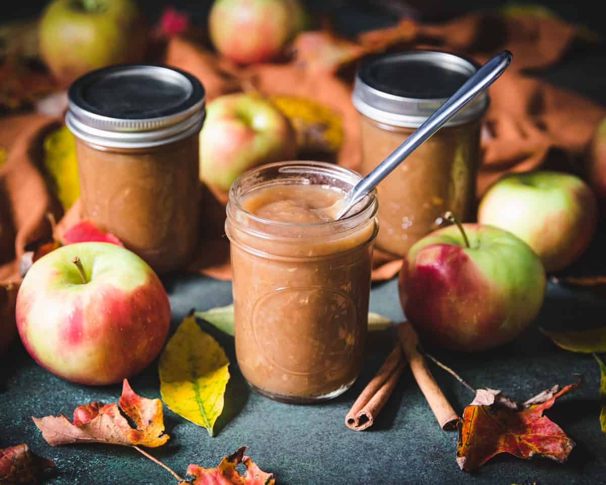 several jars of spiced apple butter, one open with a knife